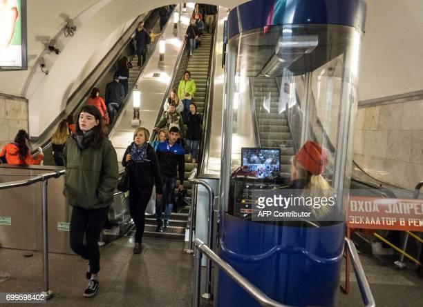 An employee watch the commuters and security monitors at a metro station in StPetersburg on June 22 2017 / AFP PHOTO / Mladen ANTONOV