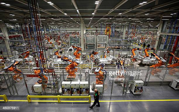 An employee watches as a ABB Ltd automated robots work on Mini automobile parts produced by Bayerische Motoren Werke AG as they move along the...