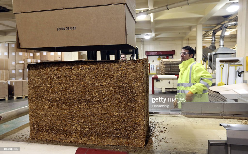 An employee watches as a colleague uses a fork lift truck to empty a block of raw tobacco onto a conveyor belt ahead of cigarette and rolling tobacco manufacture at Imperial Tobacco Group Plc's factory in Nottingham, U.K., on Friday, Feb. 1, 2013. Imperial Tobacco Group Plc is Europe's second-biggest tobacco company and generates about 40 percent of its profit from the region. Photographer: Chris Ratcliffe/Bloomberg via Getty Images