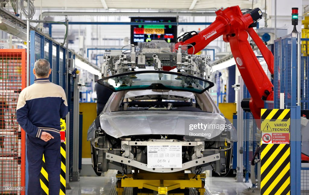 An employee watches as a Comau SpA robot positions a windscreen over the bodyshell of a Maserati Quattroporte luxury automobile during production at Fiat SpA's Grugliasco factory in Turin, Italy, on Wednesday, Jan. 30, 2013. Fiat SpA Chief Executive Officer Sergio Marchionne said the Italian carmaker narrowed losses in Europe in the fourth quarter, helping it achieve full-year earnings that were in line with its forecasts. Photographer: Alessia Pierdomenico/Bloomberg via Getty Images
