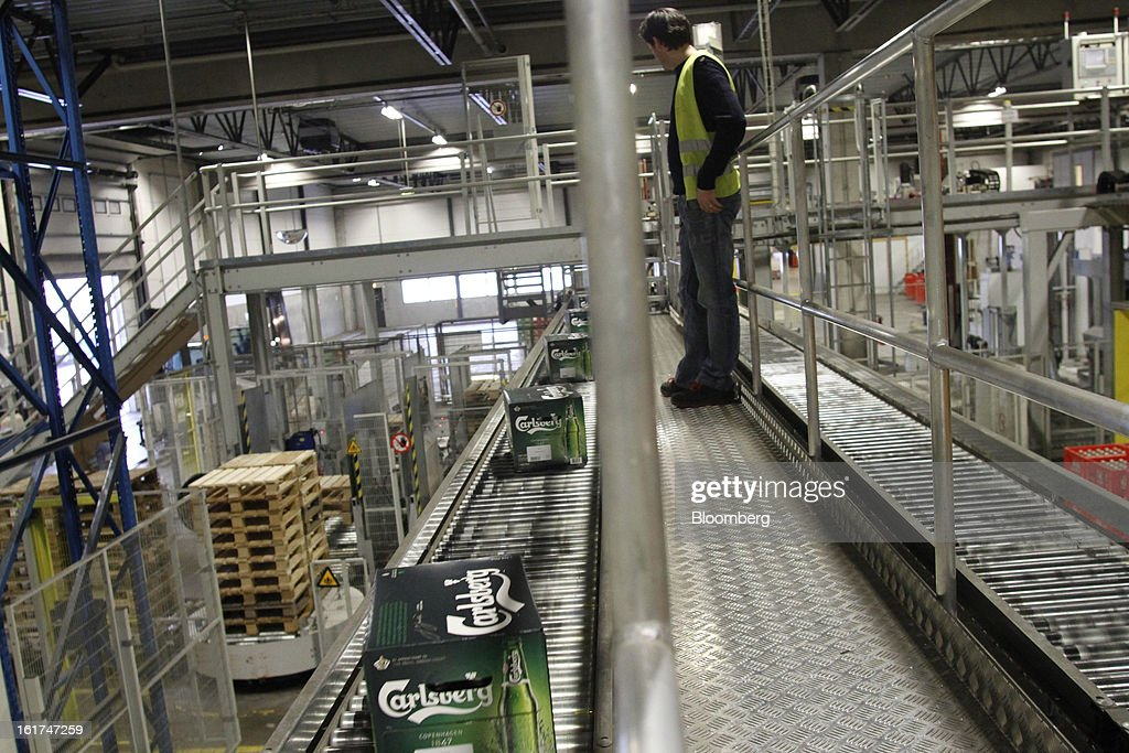 An employee watches as boxes of Carlsberg bottled beer move along a conveyor belt before an automated stacking process by machine for customer orders at the Carlsberg A/S East Terminal distribution depot in Tastrup, Denmark, on Thursday, Feb. 14, 2013. Danish brewer Carlsberg A/S owns France's biggest beer brand Kronenbourg. Photographer: Freya Ingrid Morales/Bloomberg via Getty Images