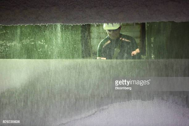 An employee watches as granules of urea or carbamide are cooled in a steel tank at the PhosAgroCherepovets fertilizer plant operated by PhosAgro PJSC...