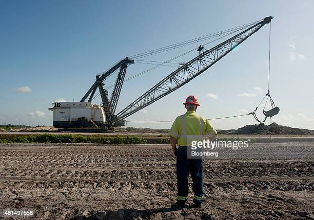 An employee watches as the bucket of a drag line unearths phosphate at the Mosaic Co South Fort Meade phosphate mine in Fort Meade Florida US on...