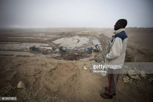 An employee watches extraction of mining material and road building work at Mining Area One in the southern coastal mines on the Skeleton Coast near...