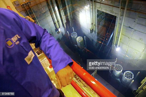 An employee watches the barrels containing high level radioactive nuclear waste being transported through water for storage in a pool to keep cool...