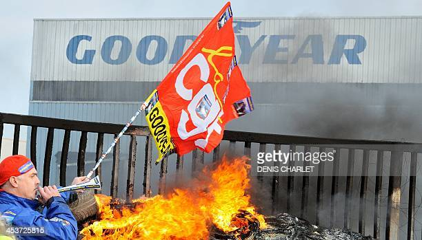 An employee waves a flag and blows a horn next to burning tyres in front the US Goodyear tyremaker site in Amiens northern France on December 5 2013...