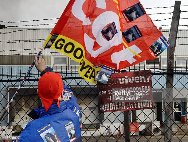 An employee waves a flag in front the US Goodyear tyremaker site in Amiens northern France on December 5 2013 during a demonstration after the...