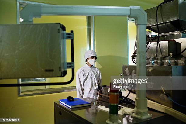 An employee wearing a face mask and protective gear monitors a machine at a Traphaco JSC manufacturing facility in Van Lam district Hung Yen Province...