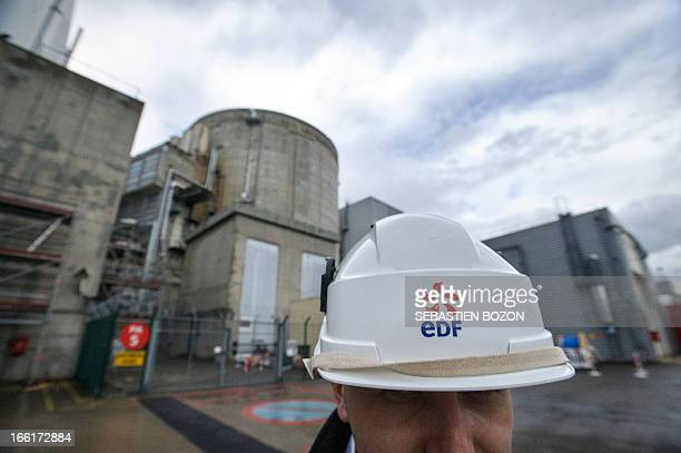 An employee wearing a helmet with the logo of French electricity company EDF is pictured in front of the Fessenheim nuclear power plant reactor...