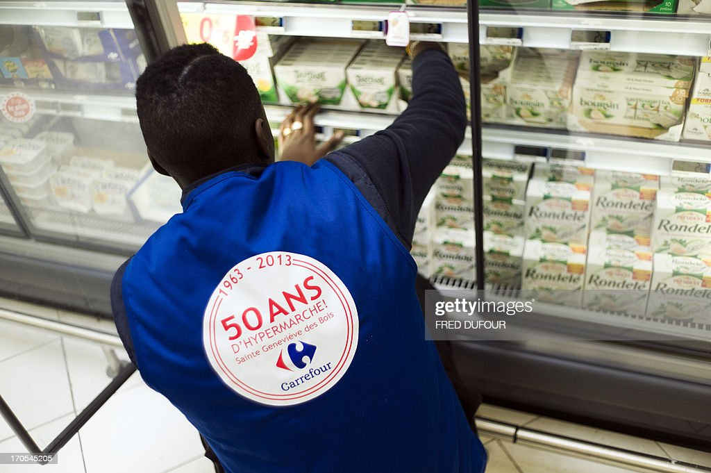 An employee, wearing a jacket reading in his back '1963-2013 - 50 years of supermarket!', stocks goods in a rack of a Carrefour supermarket, on June 14, 2013 in Sainte-Geneviève-des-Bois, outside Paris. Installed in Sainte-Geneviève-des-Bois since fifty years, on June 15, 1963, this supermarket is the first of French giant retailer Carrefour group, but also the first in France.