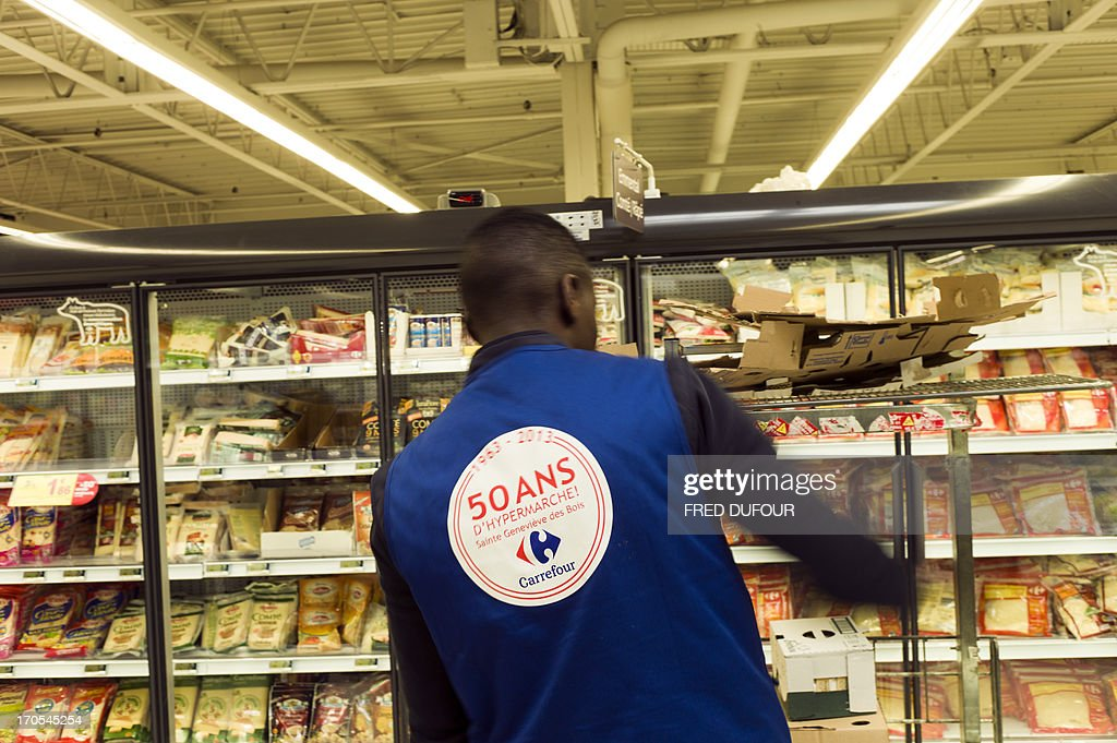 An employee, wearing a jacket reading in his back '1963-2013 - 50 years of supermarket!', stocks goods in a rack of a Carrefour supermarket, on June 14, 2013 in Sainte-Geneviève-des-Bois, outside Paris. Installed in Sainte-Geneviève-des-Bois since fifty years, on June 15, 1963, this supermarket is the first of French giant retailer Carrefour group, but also the first in France. AFP PHOTO / FRED DUFOUR