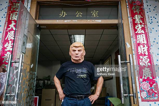 An employee wearing a mask of Donald Trump poses for a photograph at the Shenzhen Lanbingcai Latex Crafts Factory on October 18 2016 in Shenzhen...
