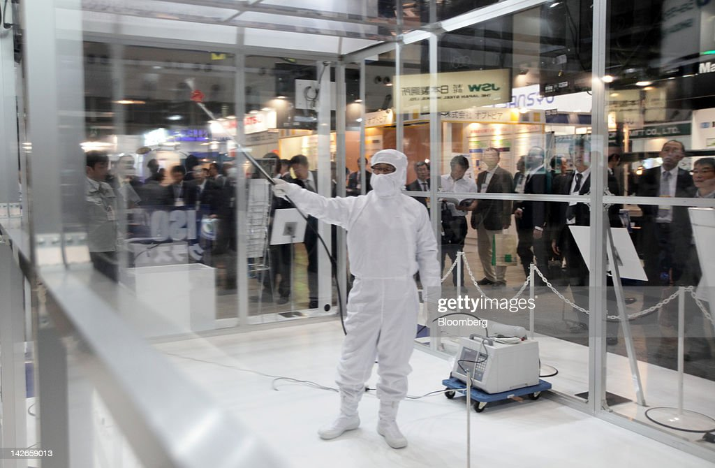 An employee wearing dust preventive workwear demonstrates in a clean room in the Koken Ltd. booth at the Finetech Japan exhibition in Tokyo, Japan, on Wednesday, April 11, 2012. Finetech Japan, the world's largest flat panel display exhibition, will be held through April 13. Photographer: Tomohiro Ohsumi/Bloomberg via Getty Images