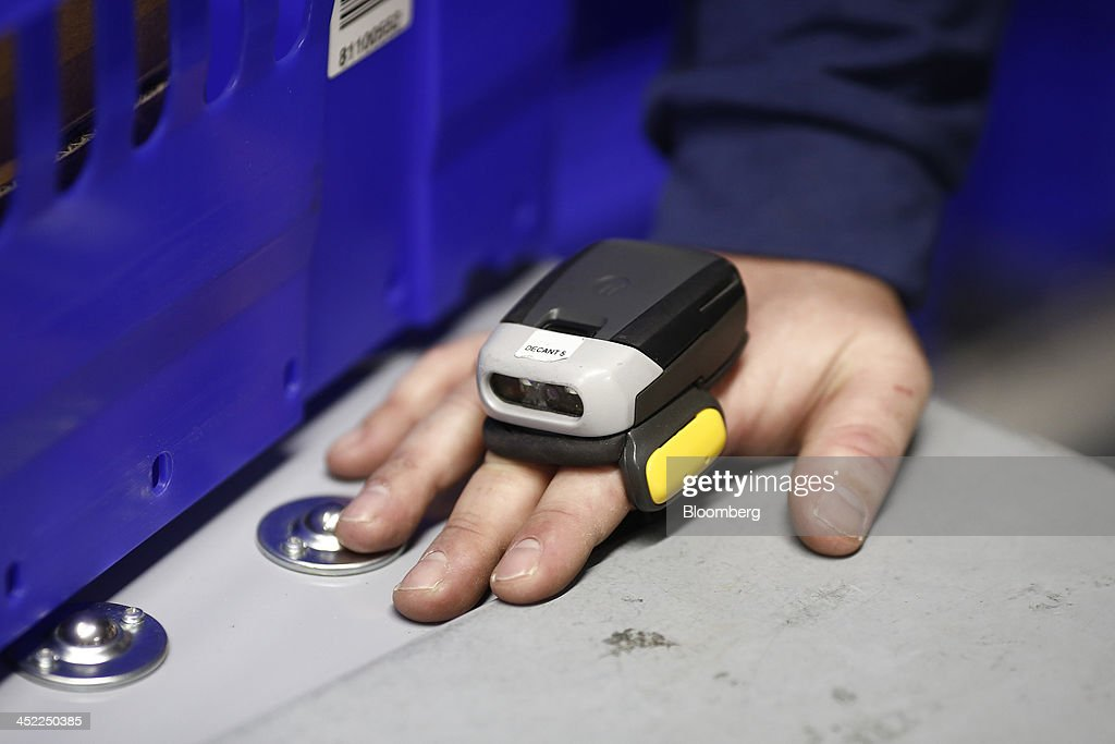 An employee wears a barcode scanner on their hand as they work to gather customer orders inside a Tesco Plc on-line distribution center, in Erith, U.K., on Wednesday, Nov. 27, 2013. Tesco Plc, the U.K.'s largest retailer, will sell land near some of its Polish hypermarkets to attract additional services around those stores. Photographer: Simon Dawson/Bloomberg via Getty Images