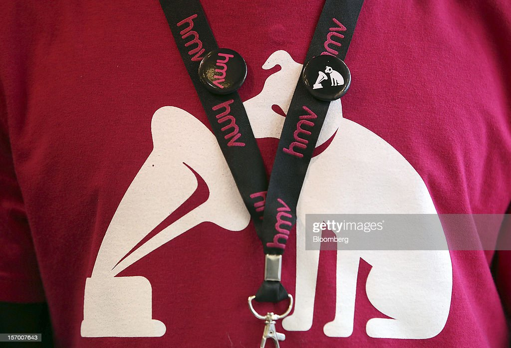 An employee wears a branded lanyard and T-shirt in this arranged photograph at a HMV pop-up store in London, U.K., on Tuesday, Nov. 27, 2012. Fashion chain Hobbs is among those that have opened pop-up stores for the first time this year, while CD and DVD retailer HMV Group Plc is adding more than usual for the holiday in an effort to win business. Photographer: Chris Ratcliffe/Bloomberg via Getty Images