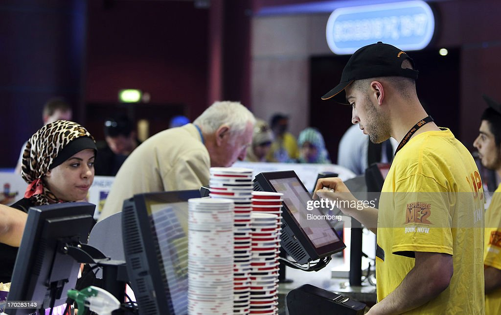 An employee wears a branded t-shirt as he serves customers at a sales counter inside a Vue Cinema, operated by Vue Entertainment Ltd., at the Westfield Stratford City retail complex in London, U.K., on Tuesday, June 4, 2013. Vue Entertainment, the U.K. cinema chain bought by private equity firm Doughty Hanson & Co., are continuing to expand in Europe, recently acquiring Poland's second-largest cinema chain Multikino. Photographer: Chris Ratcliffe/Bloomberg via Getty Images