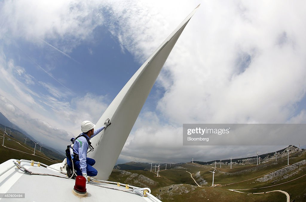 An employee wears a safety harness and hard hat as he works on the top of a wind turbine unit manufactured by Gamesa Corp. Tecnologica SA and operated by Enel Green Power SpA, the clean-energy unit of Italy's biggest utility Enel SpA at their wind farm in Frosolone, Italy, on Tuesday, July 29, 2014. Enel SpA, Italy's largest utility, will steer investments into Latin America and renewable energy as recession damps electricity demand in its biggest market. Photographer: Alessia Pierdomenico/Bloomberg via Getty Images