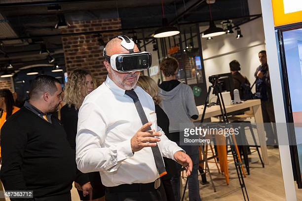 An employee wears a Samsung Galaxy Gear virtual reality headset ahead of the inauguration of an Orange SA smart store in Paris France on Tuesday Sept...
