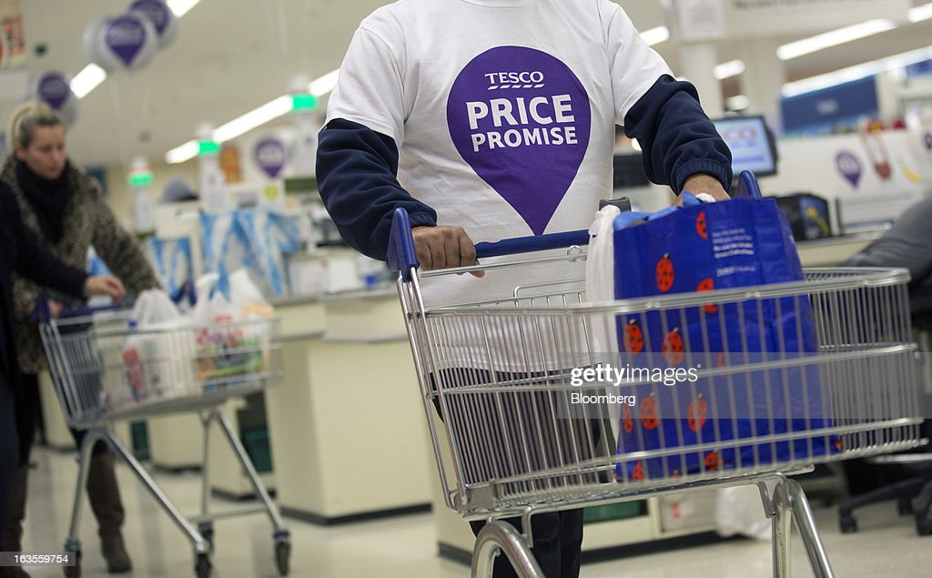 An employee wears a t-shirt displaying the 'Price Promise' logo as he pushes a shopping cart inside a Tesco Plc supermarket in the borough of Kensington in London, U.K., on Tuesday, March 12, 2013. Tesco Plc, the U.K.'s largest grocer launched a 'Price Promise', its latest initiative offering to match the price of customers' purchases to that of it's rivals, including Wal-Mart Stores Inc.'s ASDA. Photographer: Simon Dawson/Bloomberg via Getty Images