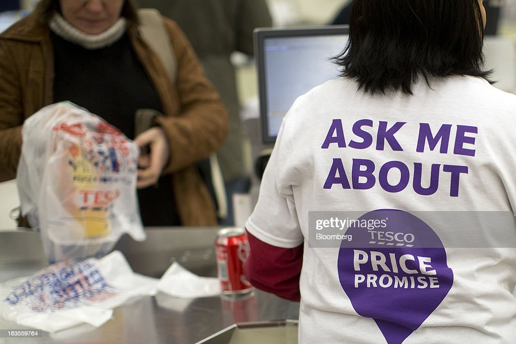 An employee wears a t-shirt displaying the Tesco 'Price Promise' logo as she serves a customer at a checkout counter inside a Tesco Plc supermarket in the borough of Kensington in London, U.K., on Tuesday, March 12, 2013. Tesco Plc, the U.K.'s largest grocer launched a 'Price Promise', its latest initiative offering to match the price of customers' purchases to that of it's rivals, including Wal-Mart Stores Inc.'s ASDA. Photographer: Simon Dawson/Bloomberg via Getty Images