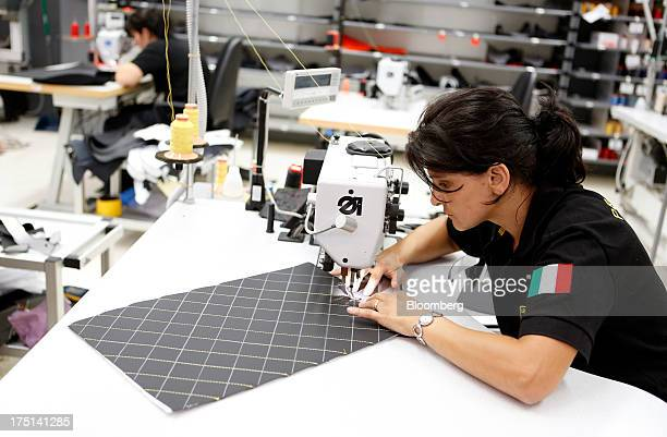 An employee wears an Italian national flag on her shirt sleeve as she prepares leather upholstery for the interior of a sports car at the Lamborghini...