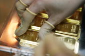 An employee wears gloves to hold a 100g gold bar engraved with the logo and name of the swiss bank UBS on April 6 2009 at a plant of gold refiner and...