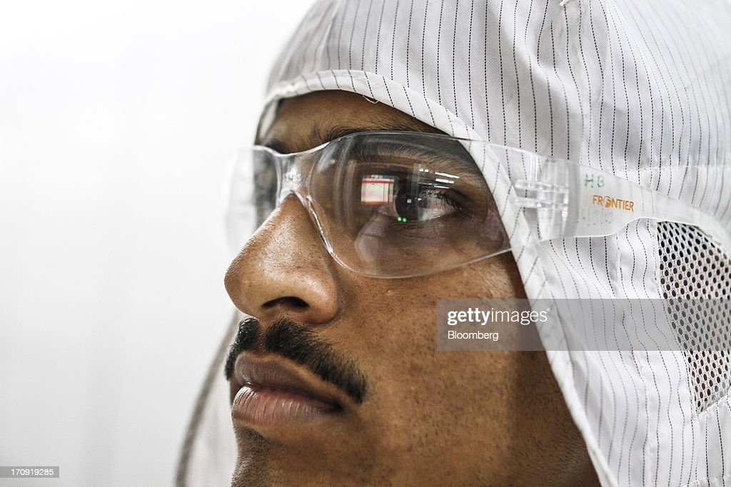 An employee wears safety glasses on the solar cell production line at the Tata Power Solar Systems Ltd. manufacturing plant in Bangalore, India, on Tuesday, June 11, 2013. Tata Groups solar unit is expanding its business building plants for customers, forecasting that offices and factories will be paying more for grid power than solar by 2016 in most Indian states. Photographer: Dhiraj Singh/Bloomberg via Getty Images