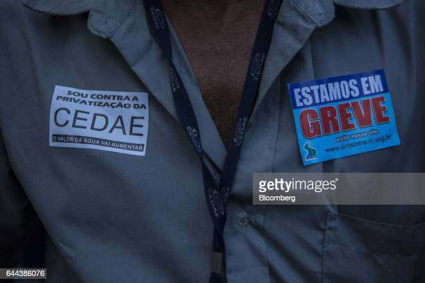 An employee wears stickers reading 'I am against the privatization of CEDAE the value of water will increase' and 'I am on strike' during a protest...