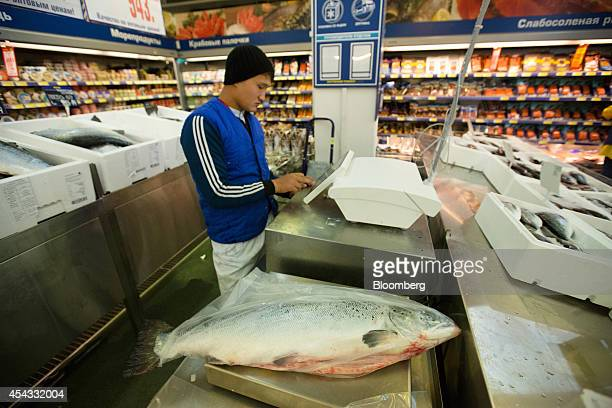 An employee weighs and prices a fresh whole salmon in the wet fish section inside a Metro Cash Carry store the Russia unit of Metro AG in Moscow...