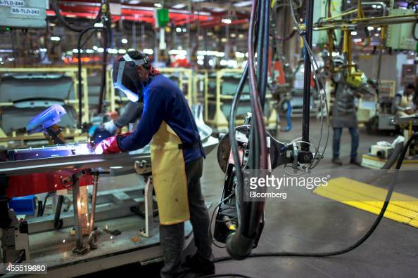 An employee welds a bodywork part of a Volkswagen AG Vento automobile on the production line at the Volkswagen India Pvt plant in Chakan Maharashtra...