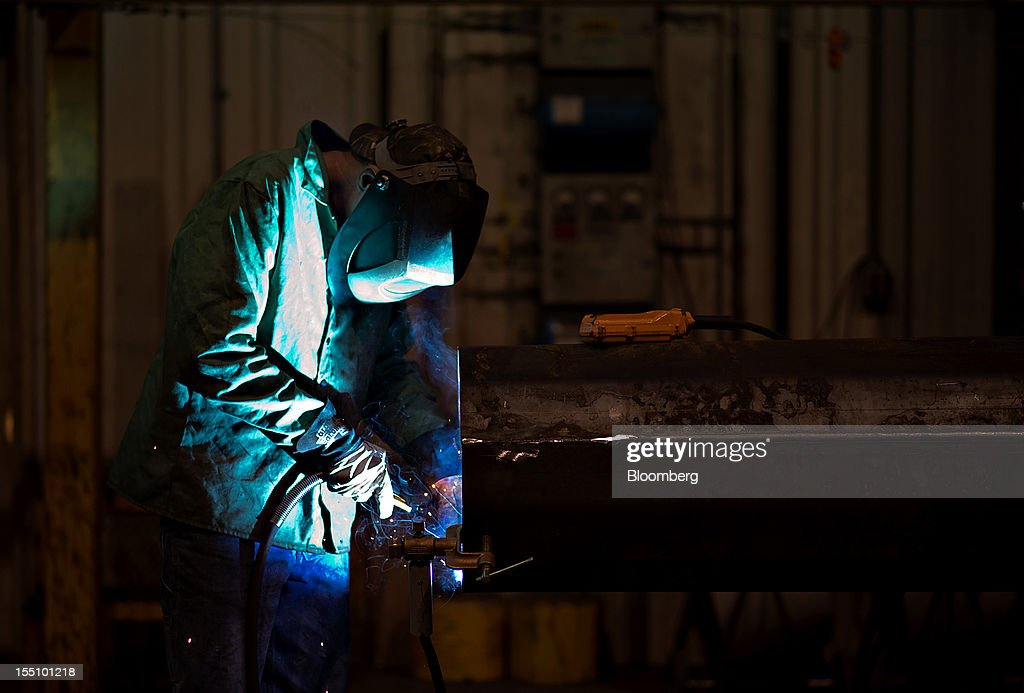 An employee welds on the interior of a steel pole at the Rohn Products LLC manufacturing facility in Peoria, Illinois, U.S., on Wednesday, Oct. 31, 2012. Manufacturing in the U.S. probably expanded in October at a slower pace, indicating the industry is providing little thrust for the expansion, economists said before a report today. Photographer: Daniel Acker/Bloomberg via Getty Images