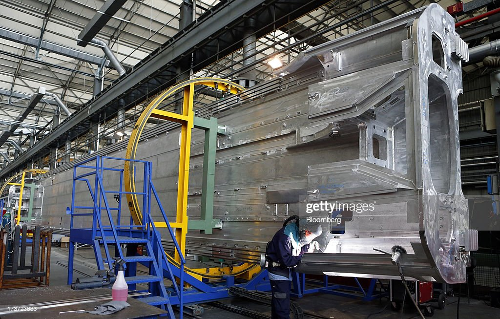 An employee welds sections of bodywork during the manufacture of Frecciarossa 1000 high-speed train carriages at AnsaldoBreda SpA's rail-car plant in Pistoia, Italy, on Tuesday, July 16, 2013. Italian business confidence rose last month after Prime Minister Enrico Letta's Cabinet passed plans to boost employment and postponed the payment of the value-added tax planned for July. Photographer: Alessia Pierdomenico/Bloomberg via Getty Images