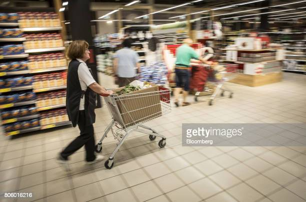 An employee wheels a shopping cart through the aisle inside a Super Konzum supermarket operated by Agrokor dd in Zagreb Croatia on Tuesday June 13...