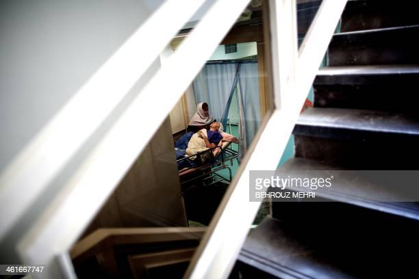 An employee wheels Iranian breast cancer patient Farvah out of the operation room after successful lumpectomy surgery at a clinic in Tehran on...