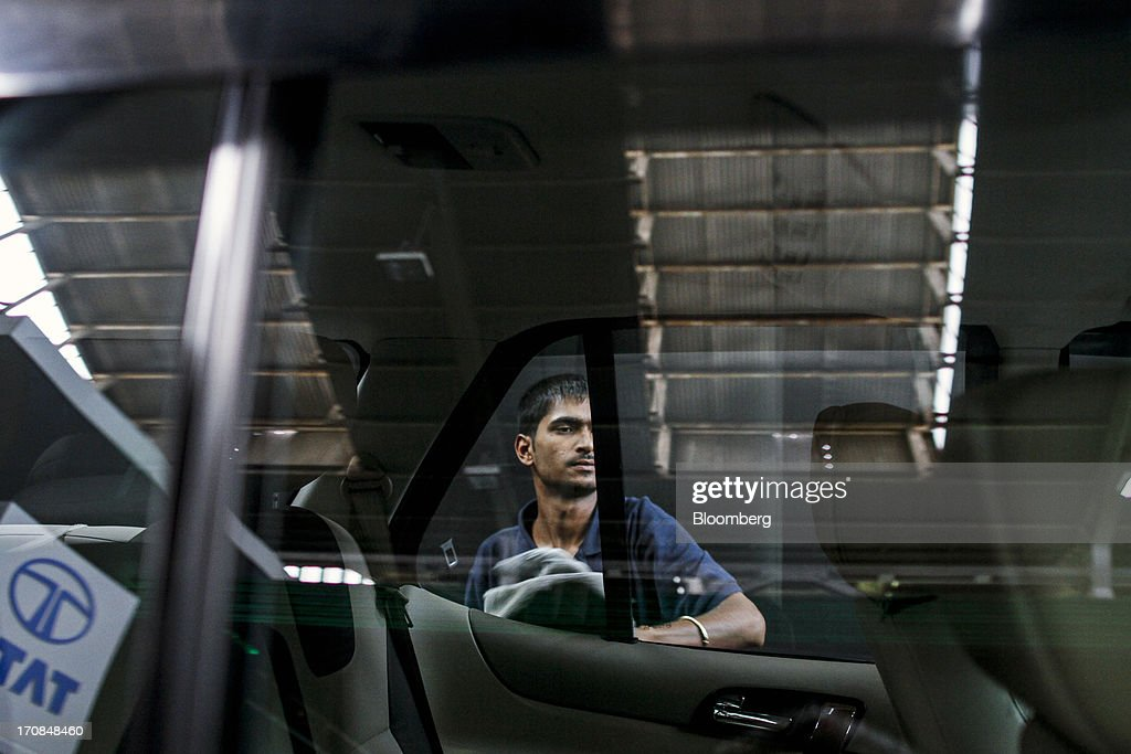 An employee wipes the window of a Tata Motors Ltd. Safari Storme sport-utility vehicle (SUV) on display during a media event in Pune, India, on Wednesday, June 19, 2013. Tata Motors announced the introduction of 8 new models today. Photographer: Dhiraj Singh/Bloomberg via Getty Images