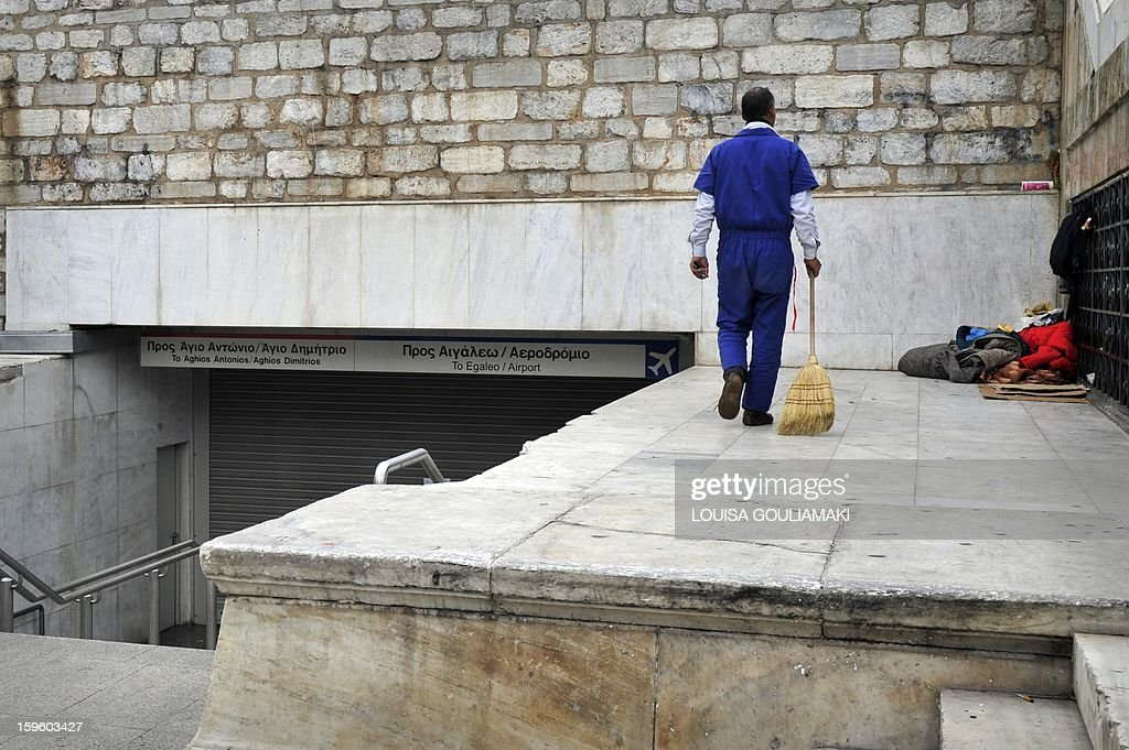 An employee with a broom walks past the closed entrance to an Athens subway station, during a 24-hour employees strike to protest salary cuts as part of the new round of the austerity measures, on January 17, 2013. The employees annouced they will continue their protest the following days. The International Monetary Fund said Wednesday it would release 3.2 billion euros ($4.3 billion) in aid to Greece that had been frozen for months amid fears about the country's ability to surmount its debt crisis. AFP PHOTO/ Louisa Gouliamaki