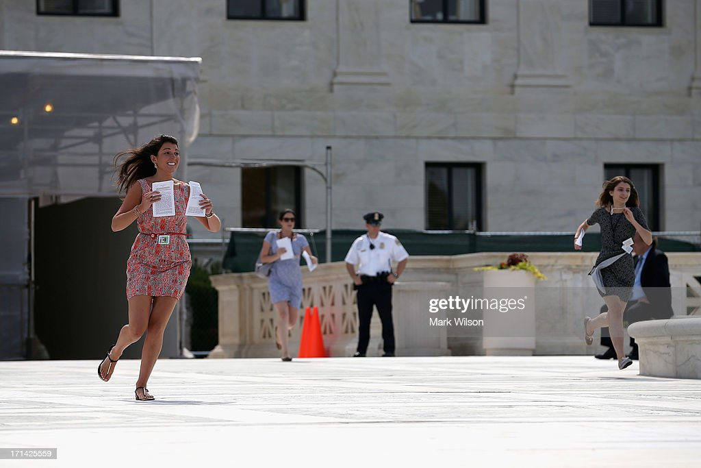 An employee with CNN (L) runs after a ruling was made on race-based college admissions, in front of the U.S. Supreme Court building June 24, 2013 in Washington DC. The high court is expected to rule this week on some high profile cases including California's Proposition 8, the controversial ballot initiative that defines marriage as between a man and a woman and an affirmative action case about the University of Texas admissions policy.