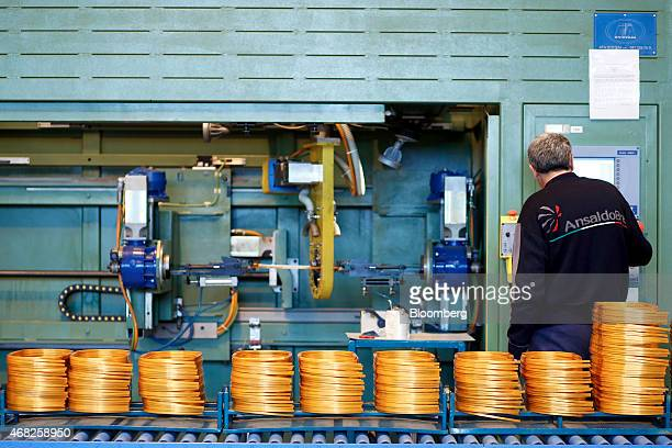 An employee work on sections of copper coils during train carriage manufacturing at AnsaldoBreda SpA's rail car plant in Naples Italy on Monday March...