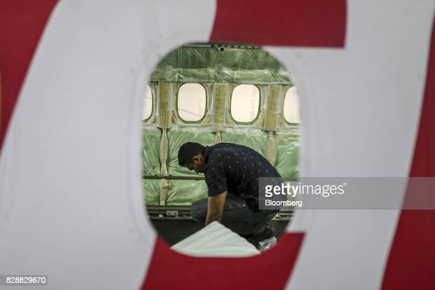 An employee working in the cabin is seen through the window of a Bombardier Inc Q400 NextGen passenger aircraft undergoing maintenance at the Air...