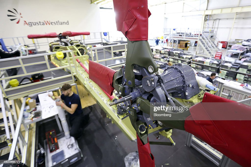 An employee works alongside the tail boom of an AW159 helicopter, produced by AgustaWestland, a unit of Finmeccanica SpA, at the company's plant in Yeovil, U.K., on Thursday, June 12, 2014. U.K. unemployment declined more than expected and industrial production rose at the fastest annual pace since 2011, according to reports released this week. Photographer: Chris Ratcliffe/Bloomberg via Getty Images