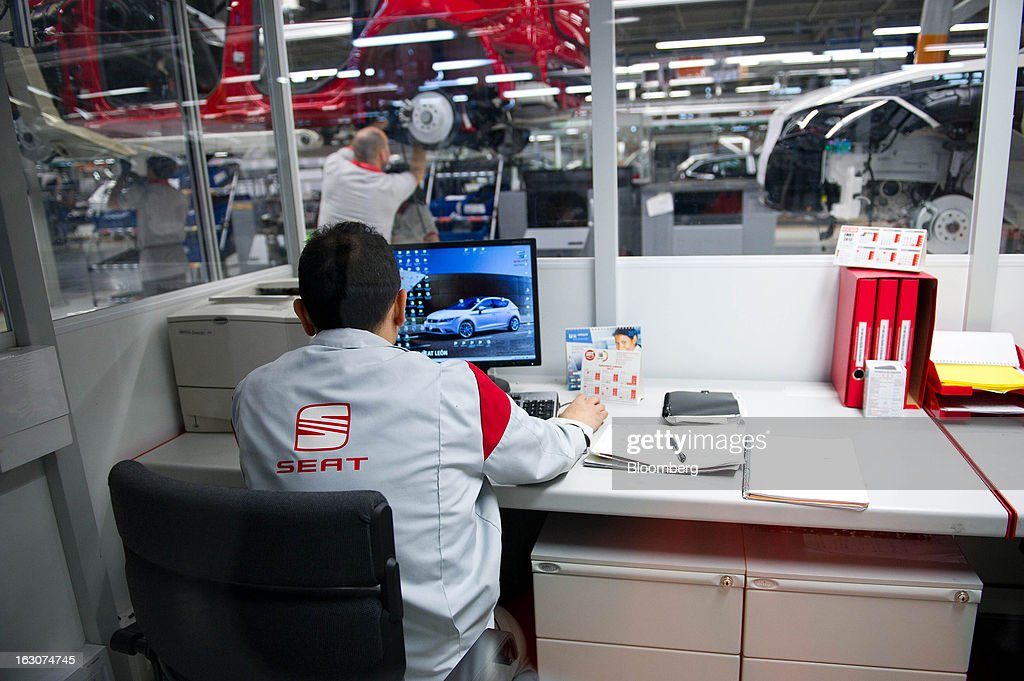 An employee works at a computer terminal in an office near the production line for Seat Altea XL automobiles at the headquarters of Seat SA in Martorell, Spain, on Thursday Feb. 28, 2013. Seat will invest 300 million euros a year in the next five years and renew its range of models, Efe said, citing an interview with James Muir, head of the Spanish unit of Volkswagen AG. Photographer: David Ramos/Bloomberg via Getty Images