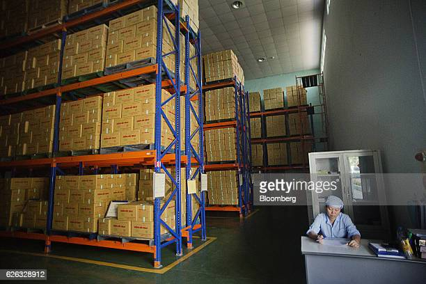 An employee works at a desk as boxes of products sit stacked in a warehouse at a Traphaco JSC facility in Van Lam district Hung Yen Province Vietnam...