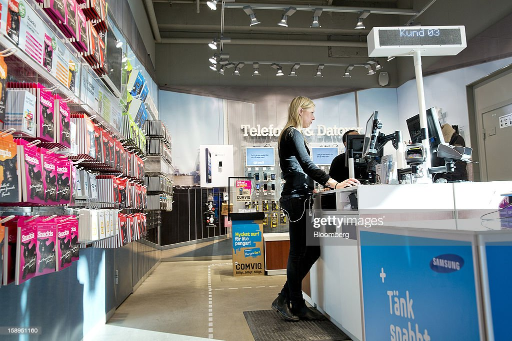 An employee works at a service counter inside a Tele2 AB store at the Farsta Centrum shopping center in Stockholm, Sweden, on Friday, Jan. 4, 2013. OAO Rostelecom's largest owner after the Russian state, Konstantin Malofeev, is urging the country's dominant fixed-line operator to buy the local unit of Sweden's Tele2 AB to form a fourth nationwide wireless carrier. Photographer: Casper Hedberg/Bloomberg via Getty Images