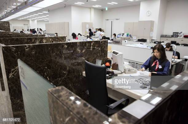 An employee works at a teller station at the Mizuho Bank Ltd branch inside the Mizuho Financial Group Inc headquarters in Tokyo Japan on Friday April...
