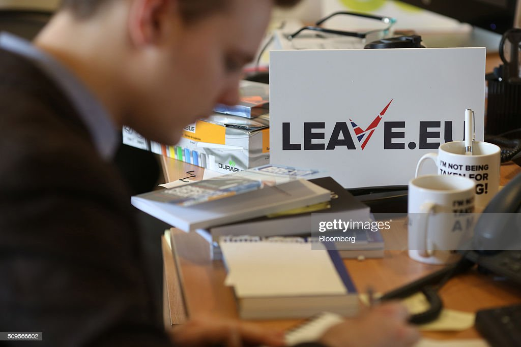 An employee works at his desk as a branded placard sits on his desk inside the Leave.EU campaign headquarters, a party campaigning against Britain's membership of the European Union, in London, U.K., on Thursday, Feb. 11, 2016. Britain's economy could be thrown off track by the planned referendum on European Union membership, according to the Confederation for British Industry. Photographer: Chris Ratcliffe/Bloomberg via Getty Images