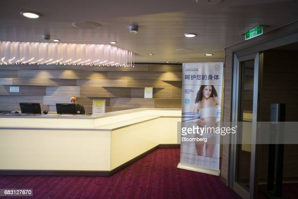 An employee works behind a counter as an advertisement for spa treatments is displayed inside the Vitality Spa on board the Ovation of the Seas...
