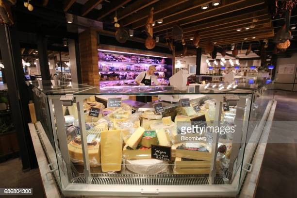 An employee works behind the cheese counter inside the new Eataly food store operated by Eataly Net Srl at the Kievsky shopping mall in Moscow Russia...