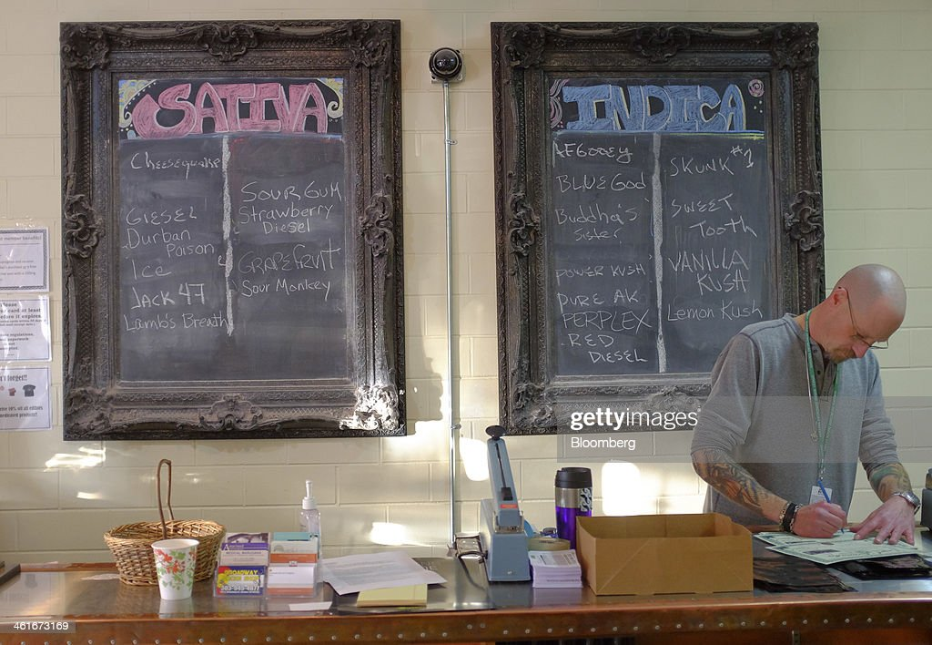 An employee works below a menu board inside the Evergreen Apothecary in Denver, Colorado, U.S., on Thursday, Jan. 9, 2014. Colorado has just legalized the commercial production, sale, and recreational use of marijuana, while Washington State will begin its own pot liberalization initiative at the end of February. On Jan. 8, New York Governor Andrew Cuomo said his state would join 20 others and the District of Columbia in allowing the drug for medical purposes. Photographer: Matthew Staver/Bloomberg via Getty Images