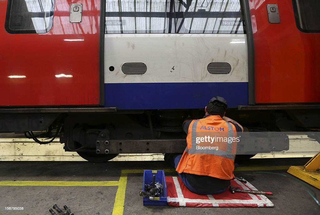 An employee works beneath a carriage of a London Underground Northern Line train at Alstom SA's Traincare Centre in the Golders Green district of London, U.K., on Wednesday, Nov. 21, 2012. Transport for London (TFL), who oversee the U.K. capital's public transport system, issued 300 million pounds ($476 million) of bonds five months ahead of schedule to take advantage of investor demand as it continues its 35 billion-pound transport investment program. Photographer: Chris Ratcliffe/Bloomberg via Getty Images