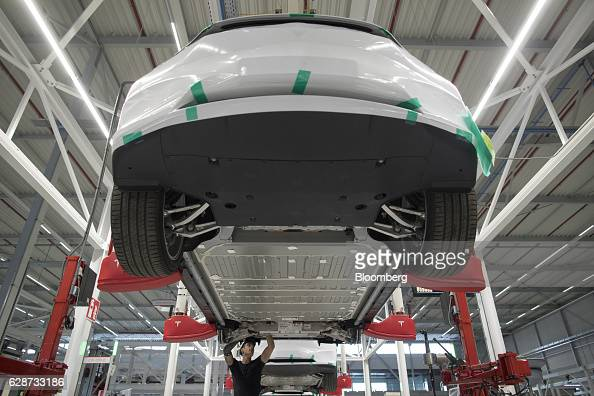An employee works beneath a Tesla Model X sports utility vehicle during assembly for the European market at the Tesla Motors Inc factory in Tilburg...